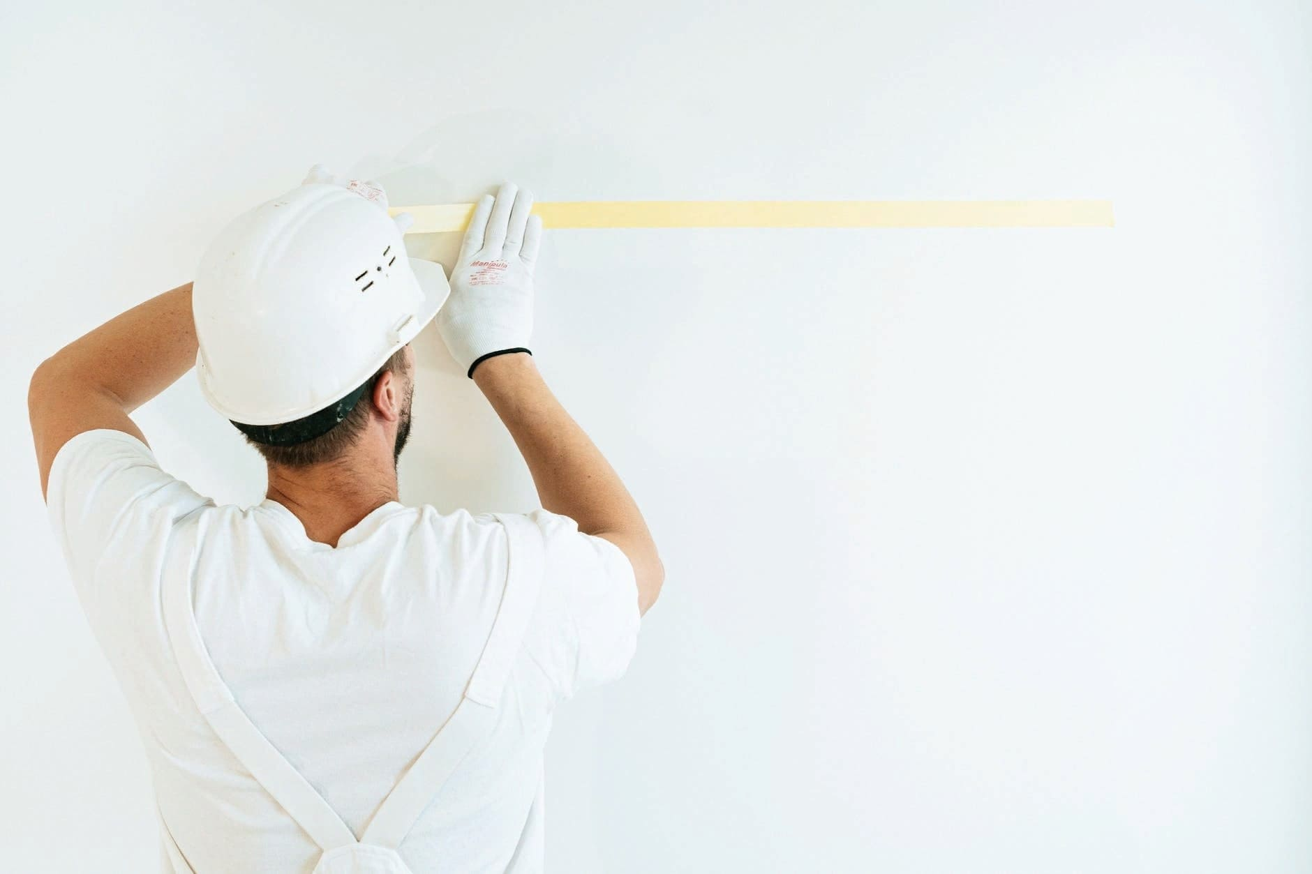 Строитель клеит ленту на стену